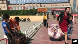 ویغور بچے ایک بس سٹاپ پر انتظار کرتے ہوئے۔ فائل فوٹو