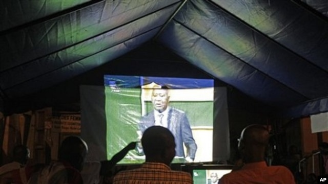 People watch on a big screen as Ivory Coast President Laurent Gbagbo talks during a live debate on national television with Ivory Coast opposition leader Alassane Ouattara in Abidjan, 25 Nov 2010