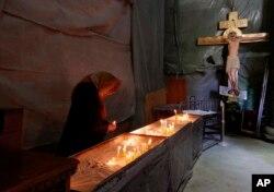 Starica pali sveće u Hramu svetog Save u Beogradu, tokom proslave Uskrsa bez prisustva vernika zbog epidemije koronavirusa, Srbija, 19. aprila 2020. (AP Photo/Darko Vojinović)