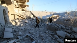 Residents inspect damage after airstrikes by pro-Syrian government forces in Anadan city, about 10 kilometers away from the towns of Nubul and Zahraa, Northern Aleppo countryside, Feb. 3, 2016.