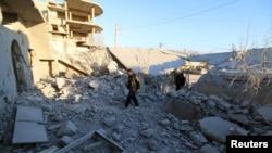 Warga memeriksa kerusakan setelah serangan udara yang dilancarkan oleh pasukan pro pemerintah Suriah di kota Anadan, sekitar 10 km dari kota Nubul dan Zahraa, Aleppo utara, Suriah, 3 Februari 2016.