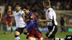 Lionel Messi na FC Barcelona yana kokarin ketawa da kwallo a tsakanin Ever Banega da Marius Stankevicius na Valencia a karawarsu ta ranar 2 Maris 2011.