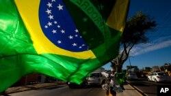 Un vendedor ondea una bandera brasileña en Fortaleza, Brasil.