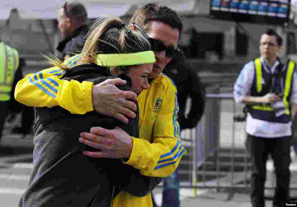 A woman is comforted by a man near a triage tent set up after explosions went off at the 117th Boston Marathon in Boston, Massachusetts, April 15, 2013.