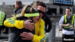Une femme est réconfortée par un homme près d'une tente de triage mis en place pour le marathon de Boston après des explosions au 117e marathon de Boston à Boston, Massachusetts 15 avril, 2013. REUTERS / Jessica Rinaldi