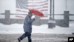 A pedestrian passes in front of an American flag as snow falls in Manchester, N.H., Feb. 5, 2016.