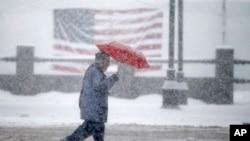 Seorang pejalan kaki melewati bendera AS sementara salju turn di Manchester, N.H., 5 Februari 2016.