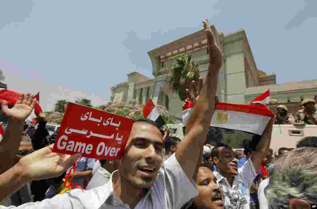 "Egyptians celebrate after Egypt's chief justice Adly Mansour is sworn in as the nation's interim president, July 4, 2013. Arabic reads, "" bye bye Morsi."""