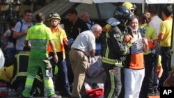 FILE - Injured people are treated in Barcelona, Spain, Aug. 17, 2017 after a van jumped the sidewalk in the historic Las Ramblas district, crashing into a summer crowd of residents and tourists.