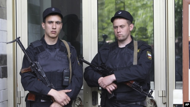 Russian police officers guard the entrance of the building where Russian opposition leader Alexei Navalny resides during a police search in Moscow, June 11, 2012.