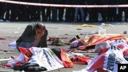 一名哭著的男子在土耳其安卡拉爆炸案現場看著死者屍體。