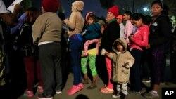 Mujeres y niños hacen fila para recibir alimentos y artículos de higiene donados en un complejo deportivo que sirve como refugio para más de 5,000 migrantes centroamericanos, en Tijuana, México, el martes 27 de noviembre de 2018.