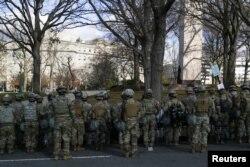 Personel militer siaga di sepanjang Pennsylvania Avenue saat iring-iringan mobil Presiden terpilih AS Joe Biden tiba di Capitol AS, di Washington, AS, 20 Januari 2021. (REUTERS / Tom Brenner)