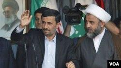 Presiden Iran Mahmoud Ahmadinejad melambai ke arah massa pendukung Hezbollah bersama komandan Hezbollah, Sheik Nabil Kaouk (kanan) di kota Bint Jbeil, Lebanon selatan, Kamis 14 Oktober 2010.