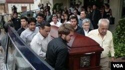 El Cónsul chileno en Maracaibo, Venezuela, Fernando Berendique, a la derecha, carga el féretro de su hija, quien murió por disparos de la policía venezolana en otro hecho revelador de la violencia destada en el país.