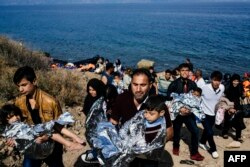 Men carry their children wrapped in emergency blankets shortly after arriving with other migrants and refugees on the Greek island of Lesbos after crossing the Aegean sea from Turkey, Oct. 18, 2015.