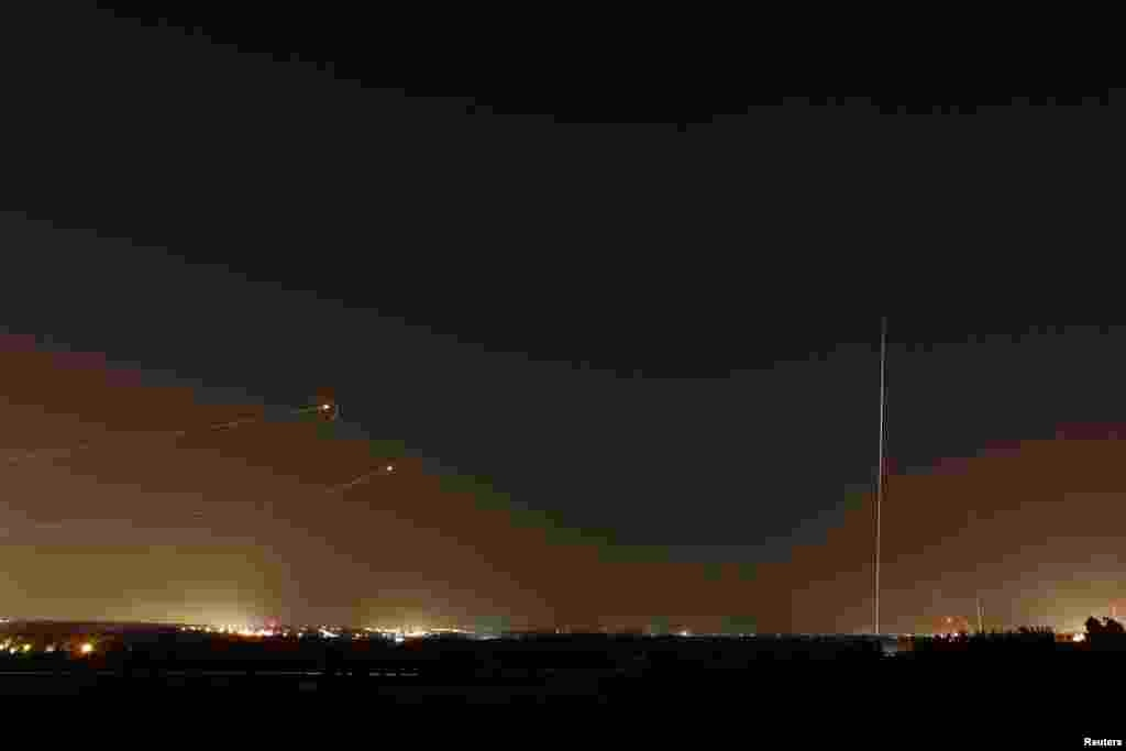 Rockets launched from the Gaza Strip towards Israel (at right) as a rocket by the Iron Dome anti-missile system (at left) is fired to intercept them, before a five-day ceasefire was due to expire, Aug. 19, 2014.