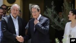 Cyprus' President Nicos Anasatsiades, right, and Turkish Cypriot leader Mustafa Akinci shake hands at Ledras palace crossing point in divided capital Nicosia in east Mediterranean island of Cyprus, June, 2, 2016.