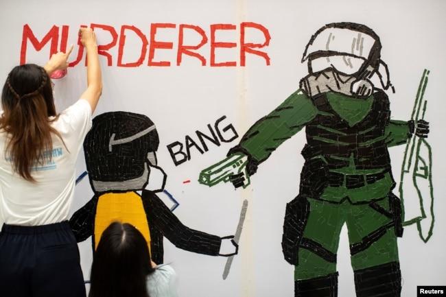 一名香港反送中抗议者在手绘一幅全副武装的蒙面港警开枪实弹射击一名抗议学生情景的壁画。(2019年10月2日)