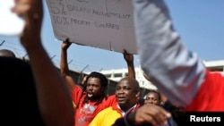 Striking members of the South African Transport and Allied Workers Union (SATAWU) hold placards outside Johannesburg's O.R. Tambo International Airport, Aug. 26, 2013.