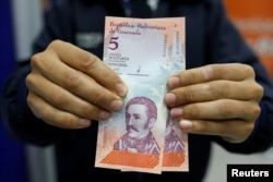 A customer shows the new five Bolivar Soberano (Sovereign Bolivar) bills, after he withdrew them from an automated teller machine at a Mercantil bank branch in Caracas, Venezuela August 20, 2018