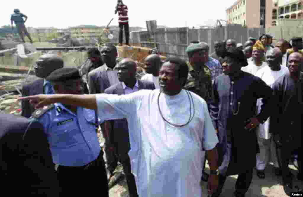 This Day's publisher Nduka Obaigbena points to a destroyed building of the newspaper during a visit by Nigerian President Goodluck Jonathan in Abuja April 28, 2012. Suicide car bombers targeted the offices of Nigerian newspaper This Day in the capital Abu