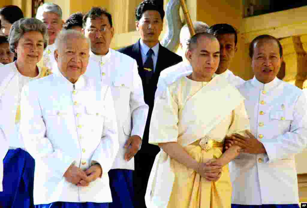 Former King Sihanouk and his son and successor King Norodom Sihamoni walk in procession at the start of coronation ceremonies at the Royal Palace in Phnom Penh, Cambodia, October 29, 2004.