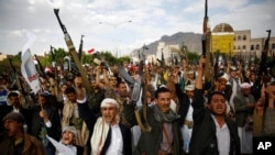 Shi'ite rebels known as Houthis hold up their weapons as they chant slogans during a rally against Saudi-led airstrikes in Sana'a, Yemen, Aug. 24, 2015.