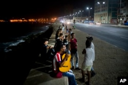 People gather along the Malecon seawall, as is customary on weekend nights, after President Raul Castro announced the death of his brother Fidel on national TV in Havana, Cuba, early Saturday, Nov. 26, 2016.