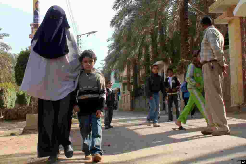 Umm Radwan walks with her son in Mit Rahina. (VOA-E.Arrott)