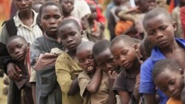 Refugee children, displaced by continued fighting in north Kivu province in the Democratic Republic of Congo, queue for food in the Nyakabande refugee transit camp in Kisoro town, July 13, 2012.