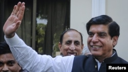 Pakistan's new Prime Minister Raja Pervez Ashraf waves to the media in Islamabad, Pakistan, June 22, 2012.