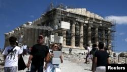 Para turis mengunjungi kuil Parthenon di atas bukit Acropolis di Athena, Yunani (foto: ilustrasi).