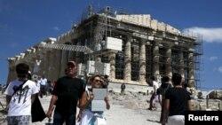 Para turis di depan kuil Parthenon di atas bukit Akropolis di Athena, Yunani (22/6). (Reuters/Alkis Konstantinidis)