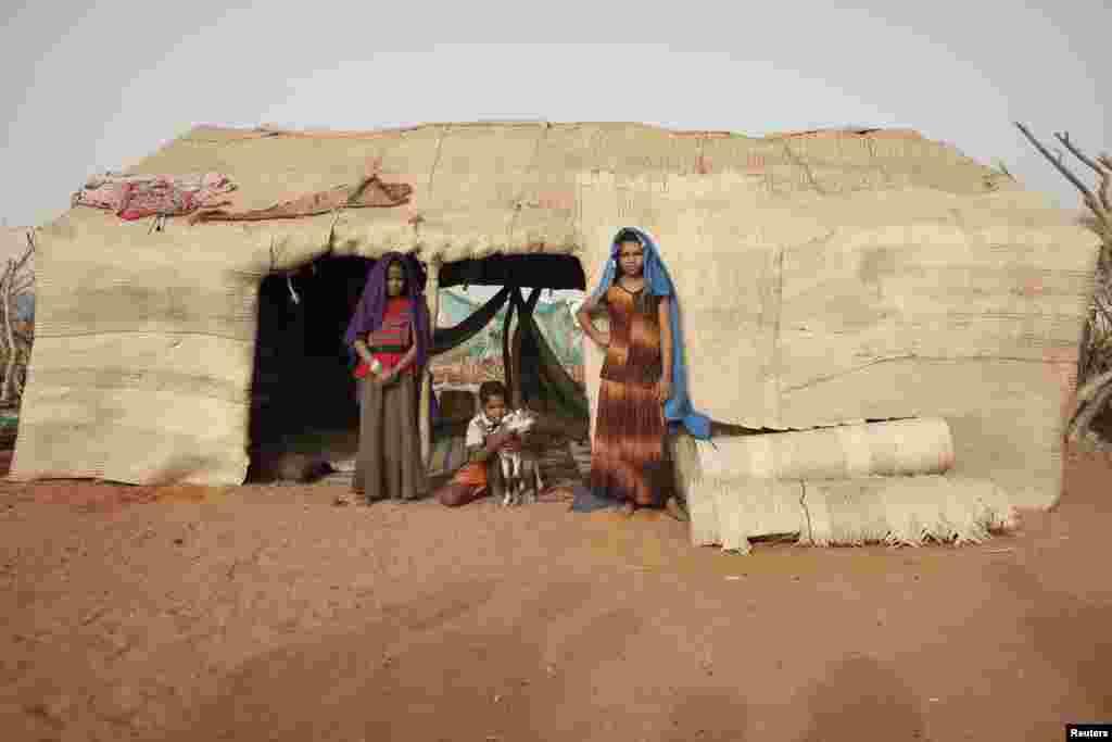Les soeurs Aicha (à gauche) et Fatima Hamadi (à droite), et leur frère de 10 ans, Omar Ould Hamadi, devant leur abri dans le camp de Mbera. Ils ont fui Tombouctou au mois de mars en compagnie de leurs parents.