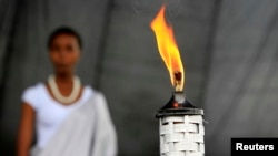 A girl stands in the background after escorting the Rwandan genocide flame, known as the 'Kwibuka' (Remembering) 20-years, at the Kicukiro Grounds as the country prepares to commemorate the 1994 Genocide in the Rwandan capital, April 5, 2014.