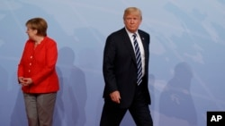 FILE - U.S. President Donald Trump walks off after being greeted by German Chancellor Angela Merkel after arriving at a G-20 Summit in Hamburg, Germany, July 7, 2017.