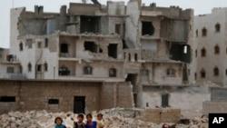 Dalam foto yang diambil pada tanggal 29 Mei 2018 ini, tampak anak-anak berjalan di depan gedung-gedung yang rusak perang di pinggiran al-Bab, Suriah utara. (Foto: AP/Lefteris Pitarakis)