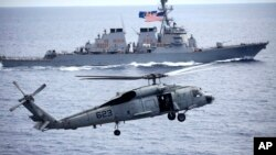 a U.S. Navy SH-60 Seahawk helicopter approaches to land on the deck of U.S. aircraft carrier, USS George Washington (CVN-73) with the backdrop of U.S. navy destroyer USS John S. McCain (DDG-56).