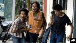 'Red shirt' anti-governement protesters carry a civilian after he was allegedly shot by a Thai army sniper near Ragprarop intersection during ongoing clashes in Bangkok, 15 May 2010