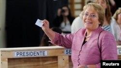 칠레 대통령 선거에 도전장을 낸 중도 좌파 성향의 미첼 바첼레트 후보가 17일 투표에 임하며 자신의 투표지를 들어 보이고 있다.