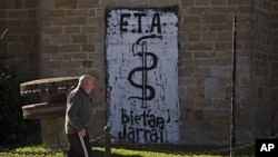 A man walks passes in front a wall painted with the anagram of the Basque separatist armed group ETA, reading '' ETA Together Always'' in Arbizu northern Spain, October 21, 2011.