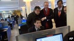 Tổng giám đốc Google Eric Schmidt (giữa), và cựu Thống đốc New Mexico Bill Richardson (thứ hai, phải) xem một sinh viên Bắc Triều Tiên sử dụng internet tại phòng thực nghiệm trong khi 2 ông đến thăm Đại học Kim Il Sung ở Bình Nhưỡng, 8/1/13