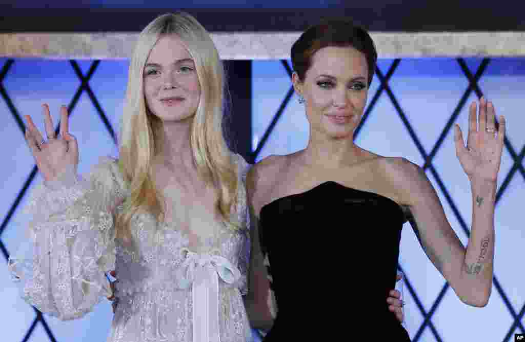 "Actresses Angelina Jolie, right, and Elle Fanning wave during the premiere of ""Maleficent"" in Tokyo, Japan."