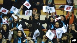 Iranian women wave flags of reformists for the parliamentary elections in a campaign rally in Tehran, Iran, Feb. 18, 2016.