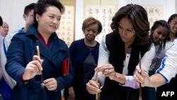 美國總統奧巴馬夫人米歇爾訪問中國期間,3月21日與中國國家主席習近平夫人彭麗媛學習拿毛筆。
