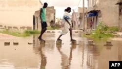 Des habitants marchent sur des briques placées dans des eaux inondées dans le quartier de Keurs Massar à Dakar le 7 septembre 2020 après de fortes pluies au Sénégal.