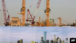 A construction area in Beijing is partly hidden by a billboard showing a view of many completed buildings.