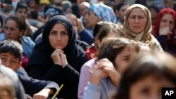 FILE - Migrants, mostly Syrians, listen to an Arabic speaker talk to them about their future as they rest in a stadium while waiting to cross to Europe near Turkey's western border with Greece and Bulgaria, in Edirne, Turkey, Sept. 23, 2015.
