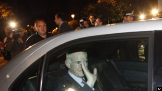 Greece's Prime Minister George Papandreou waves to journalists while exiting the Presidential Palace after a meeting with Greek President Karolos Papoulias and opposition leader Antonis Samaras, in Athens Sunday, Nov. 6 2011.